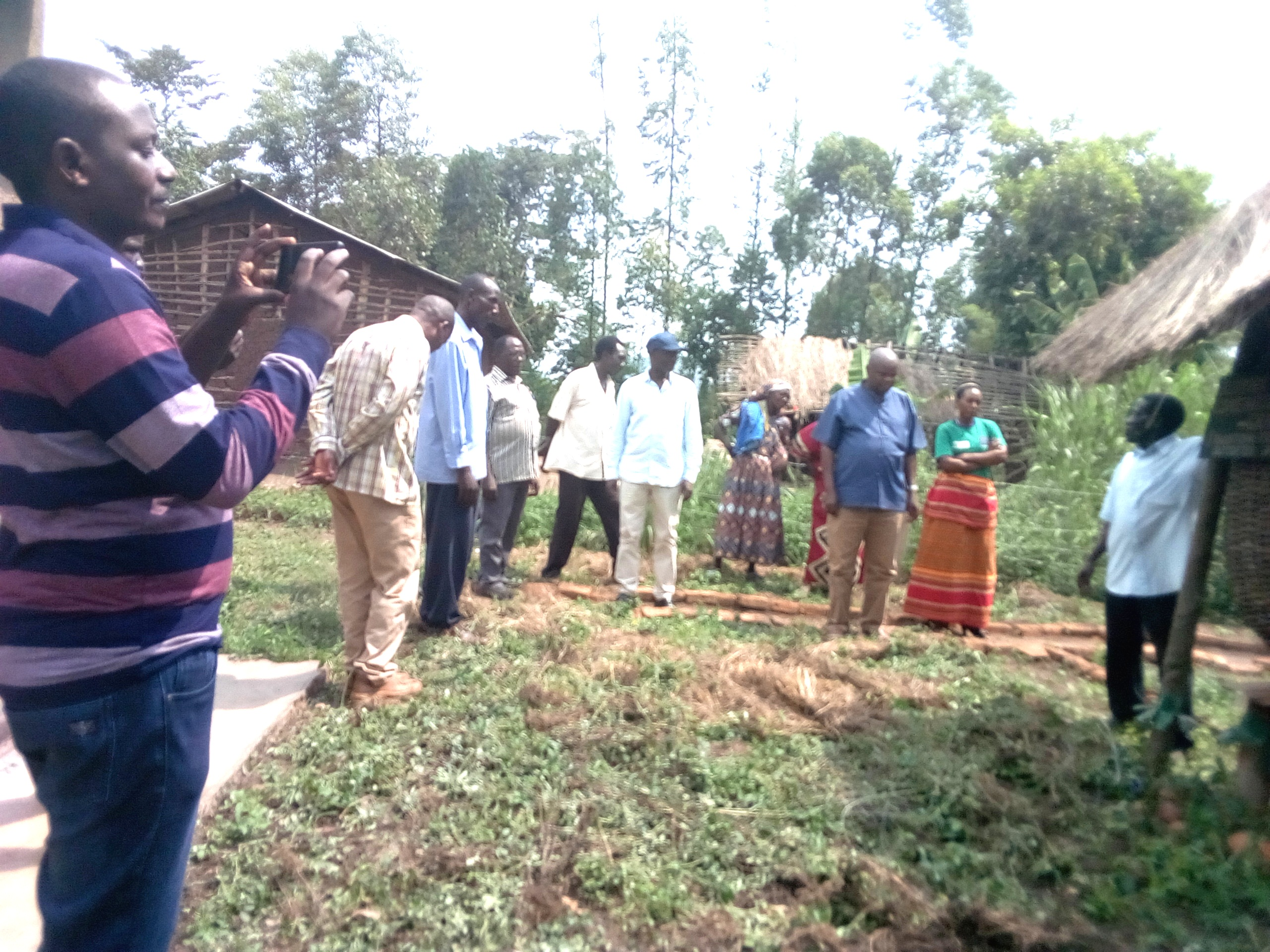 REV.FRED MUSIMENTA TAKING THE THE VISITORS AND COMMUNITY MEMBERS THROUGH A NEWSLY CONSTRUCTED GRANARY